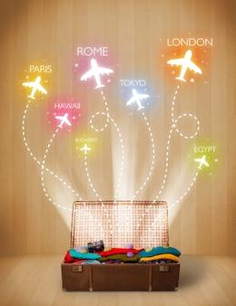 Дорожная сумка с одеждой и разноцветными самолетами, вылетающими на шероховатый фон