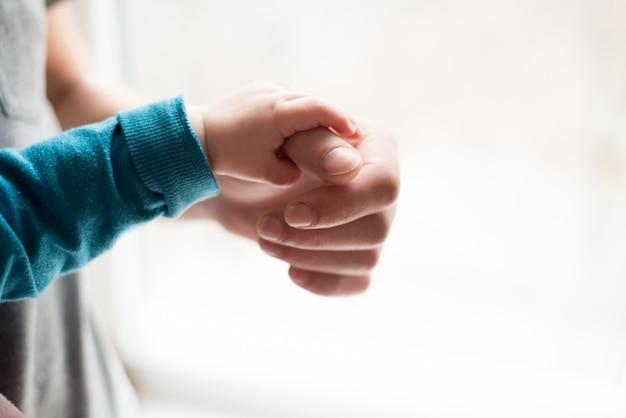 手をつないで。眠っている赤ちゃんを父親の手のクローズアップで手します。白い背景で隔離の手