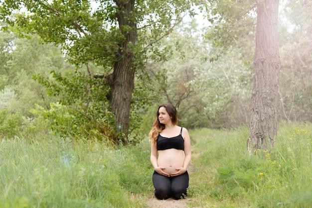 妊娠中の美しい女性ヨガ晴れた夏の日の屋外の芝生の上