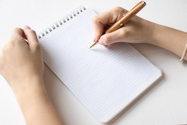 スパイラルノート、白いページとペン、女性は白い背景で隔離のペンを保持します。