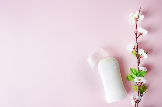 制汗剤やピンクの背景の白い花を持つ消臭剤。コピースペース