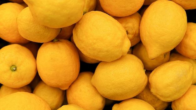 レモンの背景。市場でのレモンのカラフルな表示