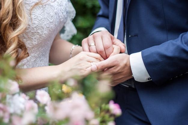 手、幸せな新郎と新婦を抱いて結婚式のカップル。