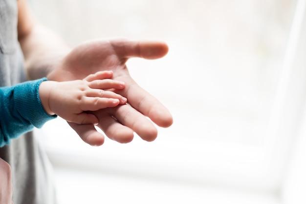手をつないで。父のクローズアップの手で眠っている赤ちゃんを手します。