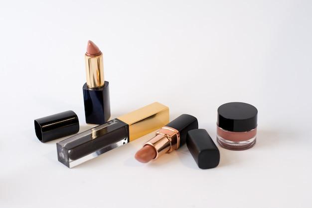 美容化粧品のフラットレイアウト画像は、口紅、クリーム、花を構成します。コピースペース、白背景