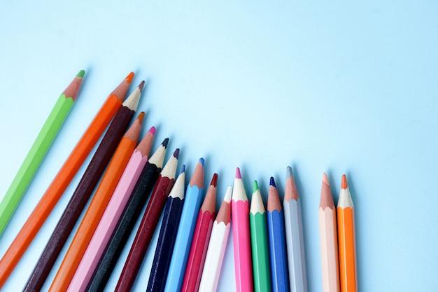 青の背景に色鉛筆をクローズアップ。学校に戻る