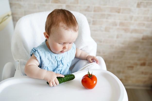 野菜を食べる赤ちゃん。小さな女の子の緑のきゅうりは日当たりの良いキッチンで手します。