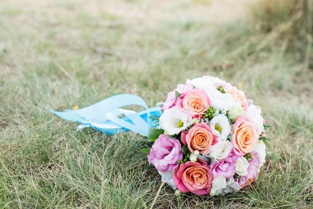 草の上のピンクと白の花を持つ花嫁のブーケ。