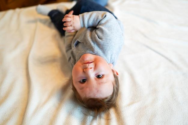 日当たりの良い白い寝室の男の子。生まれたばかりの子供がベッドでくつろいで