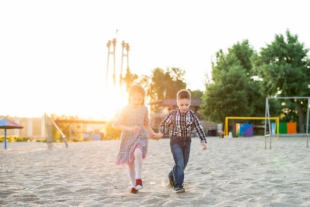 Дети веселятся на пляже. мальчик и девочка бегут и улыбаются