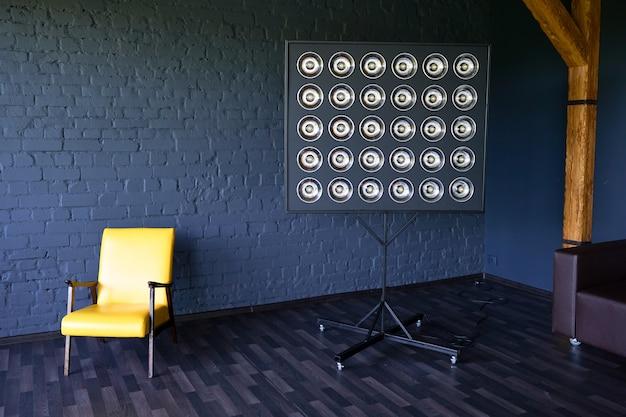Желтое кожаное кресло возле лампы. чердак черная темная кирпичная стена