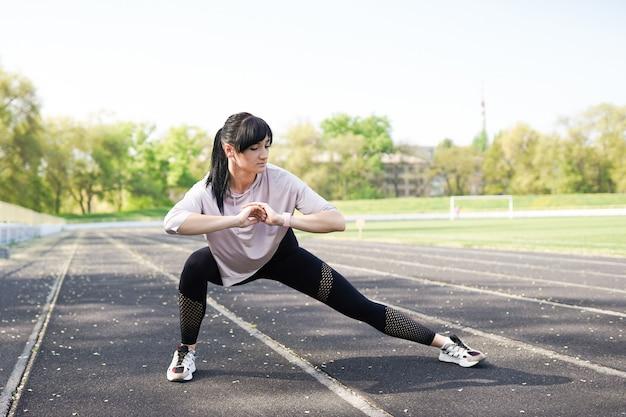 スタジアムでストレッチをしている若いフィットネス女の子。夏のスポーツ活動