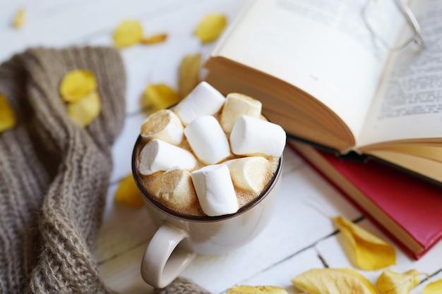 暖かいスカーフ、カカオの熱いカップと白い木の本と秋のフラットレイアウト