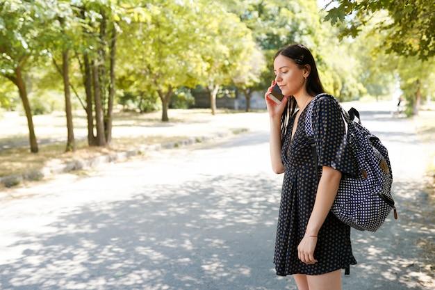 旅行..スマートフォンと車を待っている道路の近くのバッグを持つ若いカジュアルな女性