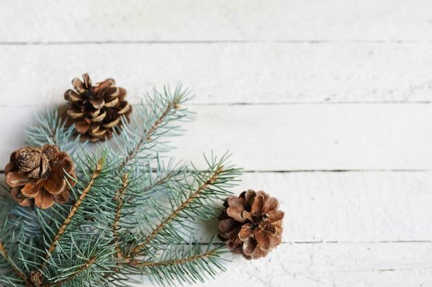 松の枝、コーン、白い木製コピースペース、お祝いの背景、休日の冬カード