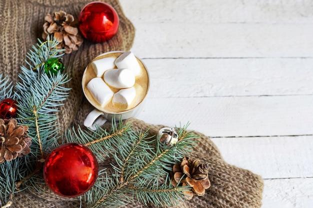 冬の温かい飲み物。赤いクリスマスのおもちゃと松と白のマシュマロとクリスマスホットチョコレートまたはココア。コピースペースの背景を持つトップビュー