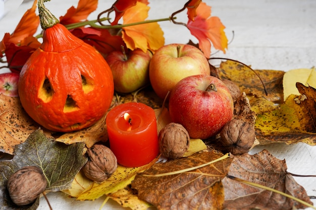 葉、リンゴ、カボチャの顔と秋のハロウィーン組成