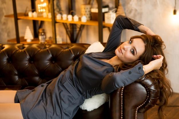 魅力的な若い女性は、スタイリッシュな服で革のソファにあります。