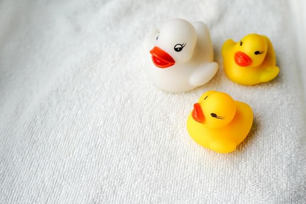 タオルの上に白と黄色のアヒルの赤ちゃんのお風呂のおもちゃ