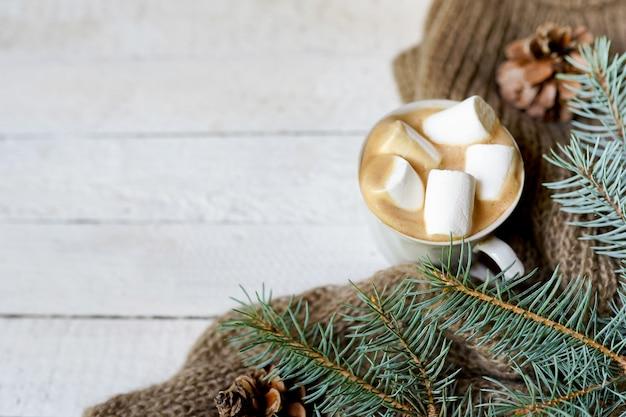 白い木製の背景、コピースペースにコーヒー、スカーフ、緑のモミの枝のクリスマスカップ