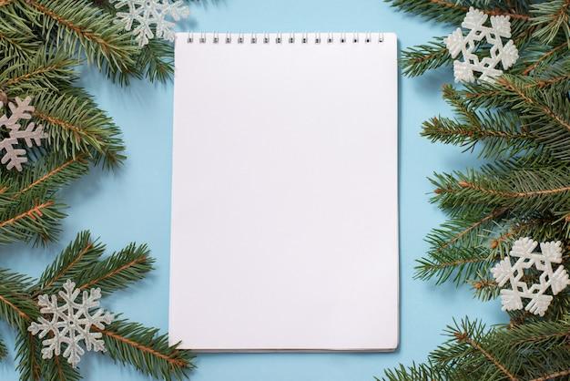 ウィッシュリスト、クリスマスツリー、雪の結晶と白いメモ帳と冬の青。コピースペース