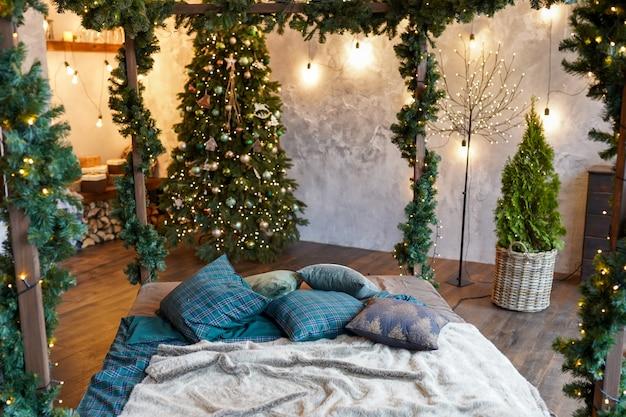インテリアと休日のコンセプト-自宅のベッドとクリスマスのガーランドライトと居心地の良いベッドルーム