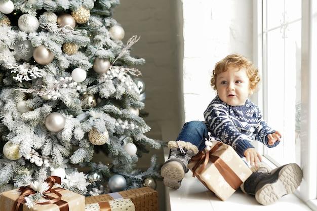 クリスマス赤ちゃん、子供が自宅でソファの上のクリスマスツリーの近くに座っギフトボックスを保持します