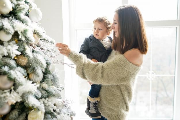 メリークリスマスとハッピーホリデー!陽気なお母さんと彼女のかわいい男の子の屋内クリスマスツリーの近く。