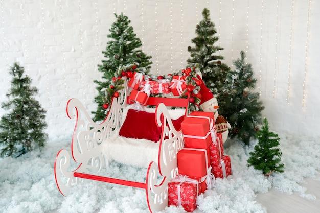 雪の上の緑のクリスマスツリーとクリスマス装飾そりと赤いギフトボックス