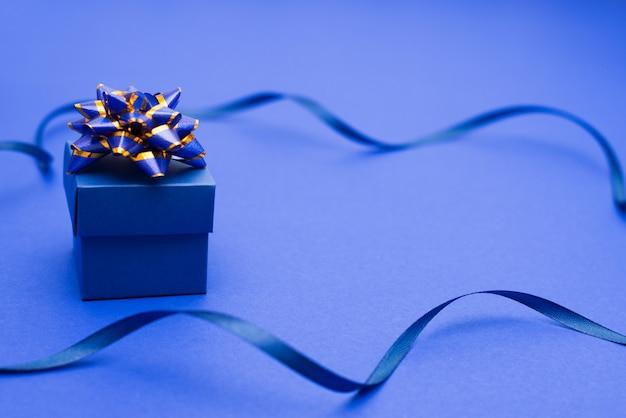 青い表面に古典的な青いリボンで包まれたギフトボックス