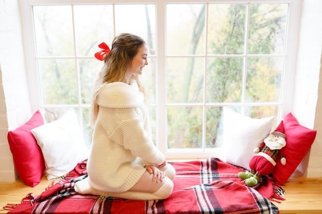 Молодая женщина с игрушкой дед мороз сидит возле окна дома