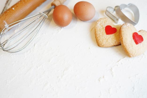 ハート型のコピースペースを持つ白いテーブルにバレンタインデーのクッキー