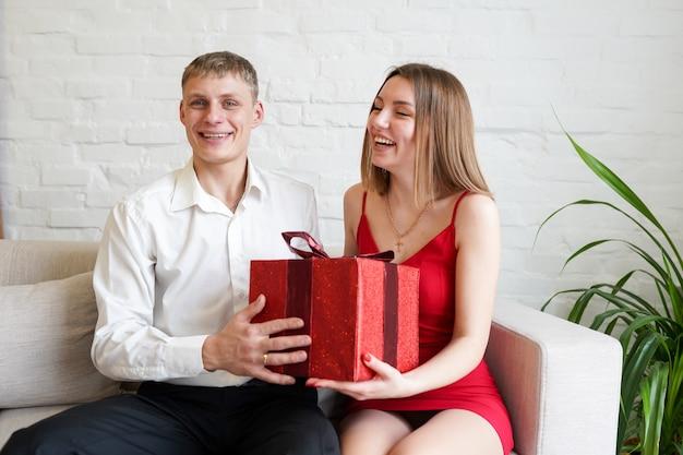 彼女のボーイフレンドから赤いリボンと美しい贈り物を受け取る笑顔の若い女性