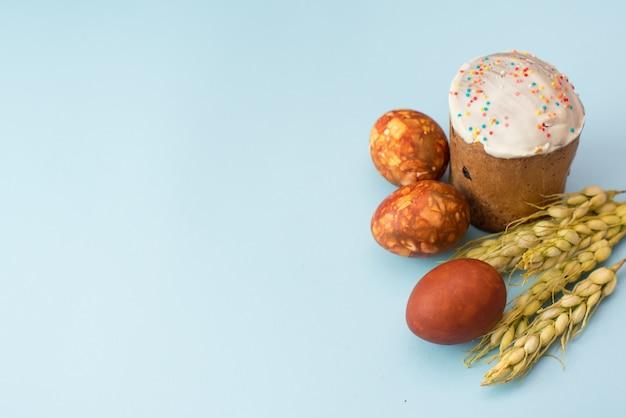 イースターケーキ、ウズラの卵、コピースペース付きのライトブルーのテーブルに茶色の小麦。