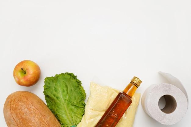 白い壁のバッグに食料の寄付。製品配信のコンセプト。重要な食品を供給する
