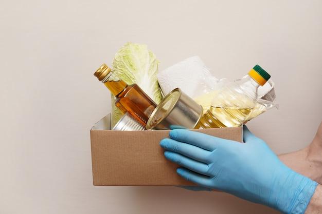 貧しい人々のための食糧の箱を持つボランティア