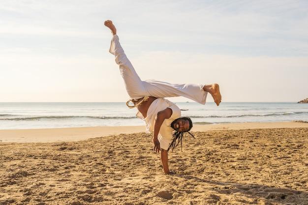 ブラジル人の男がビーチでカポエイラを訓練します。 -人、ライフスタイル、スポーツについての概念。少年はジャンプで格闘技キックを実行します。