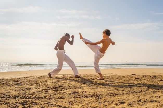 Два молодых бразильца в белых штанах практикуют капоэйру (бразильское боевое искусство, сочетающее элементы танца, акробатики и музыки) на пляже