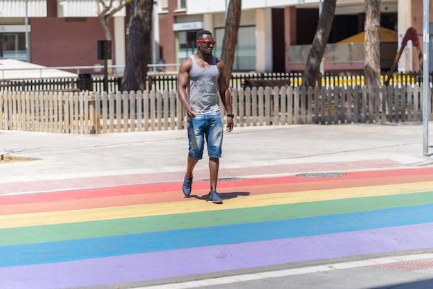 Гордость красок красит покрытия пешеходного перехода. черный человек пересекает дорогу гей-парада на перекрестке.