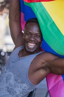 虹色の旗を保持しているキラキラひげと幸せな黒人男性