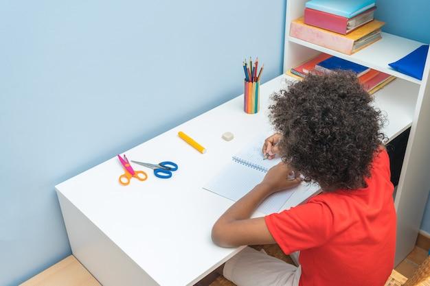 家の机に座って、宿題をしている黒人の少年。