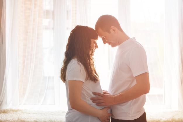 Счастливая молодая пара ожидает ребенка, стоя вместе перед окном, держа живот и думая о ребенке