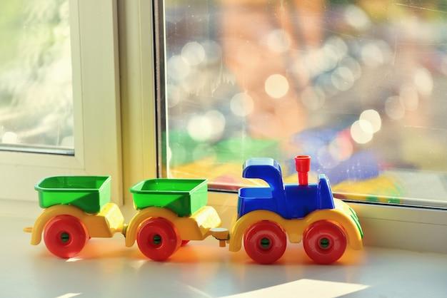 窓枠にトレーラーとプラスチックのおもちゃの列車