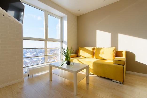 Современный уютный интерьер квартиры, гостиная с желтым диваном, белым журнальным столиком и телевизором на стене, панорамное окно с прекрасным видом на город