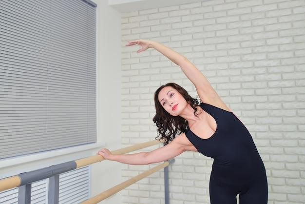 美しい女性ダンサーのダンススタジオでバレエを練習