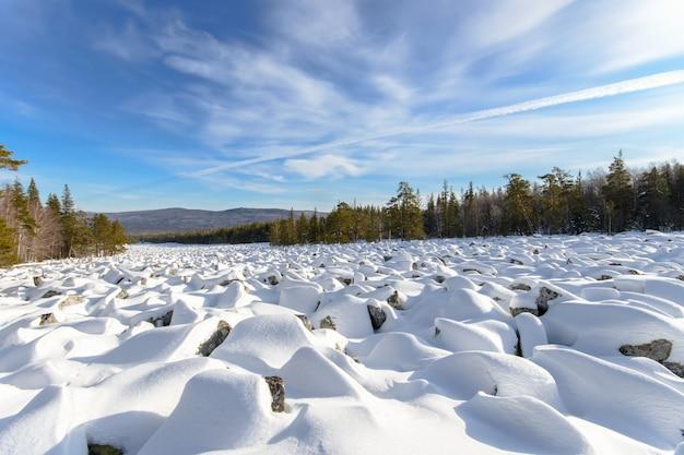 Море камней покрыто снегом, красивый зимний пейзаж.