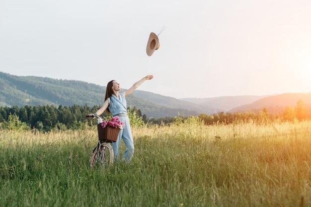 帽子を投げて笑顔の女性と日没時に山の自然を楽しんでいます。