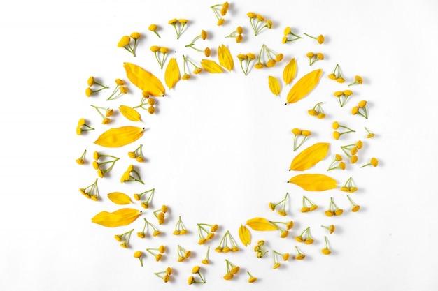 秋の創造的な構成。葉、白い背景の上の花で作られた花輪。