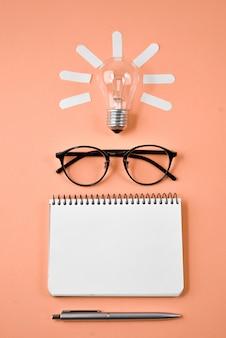 財務計画テーブルトップ、ペン、メモ帳、眼鏡、オレンジ色の背景上の電球。