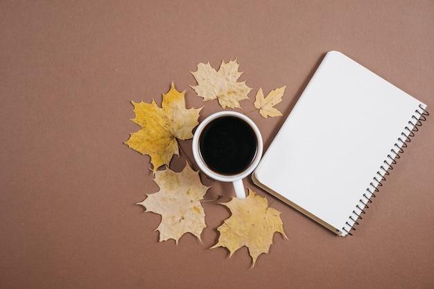 一杯のコーヒー、ノートブック、茶色の背景に秋のカエデの葉。